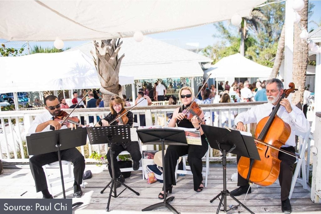 string quartet playing at a beach wedding ceremony at the Sandbar Pavilion