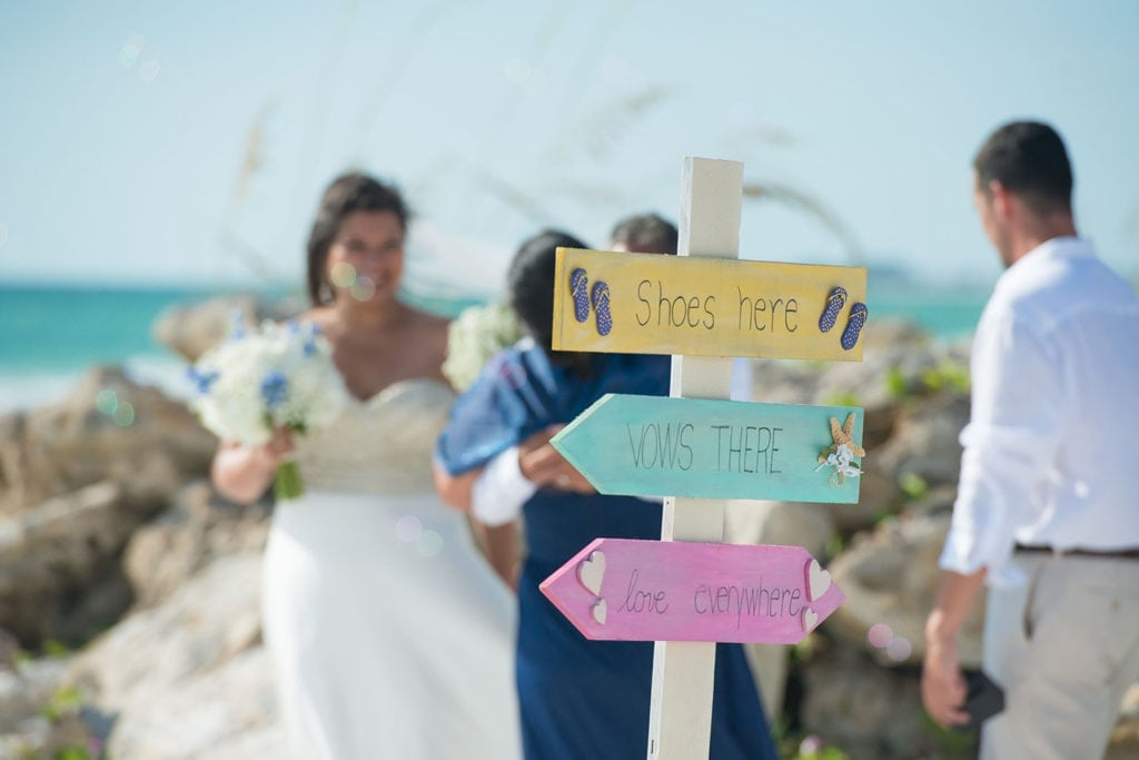 sign post at a beach wedding ceremony with the bride in the background