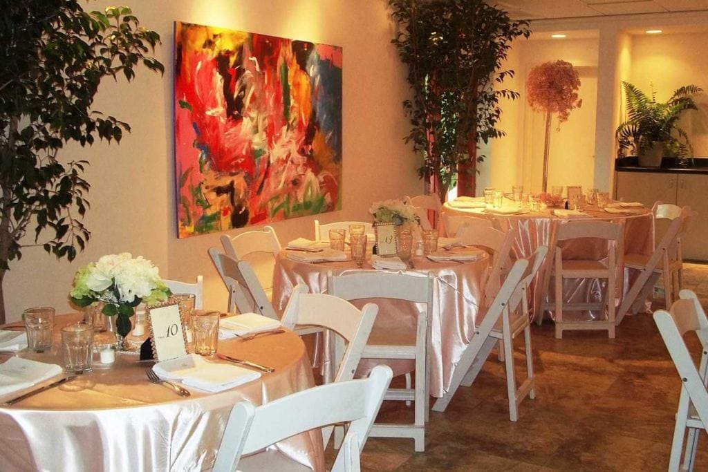 wedding reception tables in front of painting