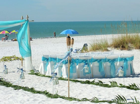decorative sashes on chairs at beach wedding ceremony