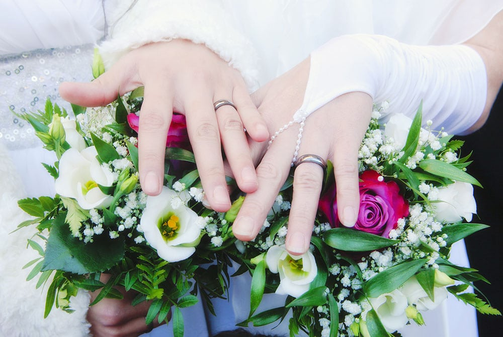 brides hands showing wedding rings