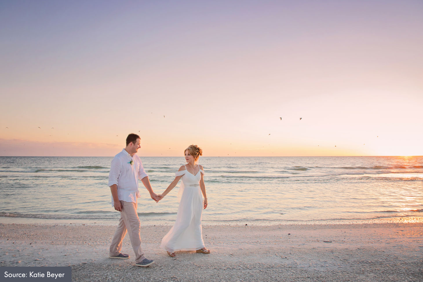 couple walking in the sand after a beach wedding