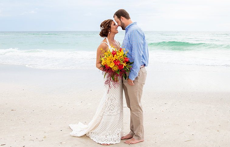 Married couple standing on the beach with a bouquet of flowers